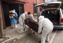 Empleados funerarios retiran el cuerpo de un hombre de 73 años mientras un miembro de la Policía de Guatemala sanitiza la entrada de la casa donde vivía, en Ciudad de Guatemala (Guatemala). EFE/Esteban Biba/Archivo