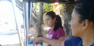"""Doña Silvia y una de sus hijas en su puesto de venta en la calle principal, frente a la Universidad de Managua, dónde era la """"Leche El Hogar"""""""