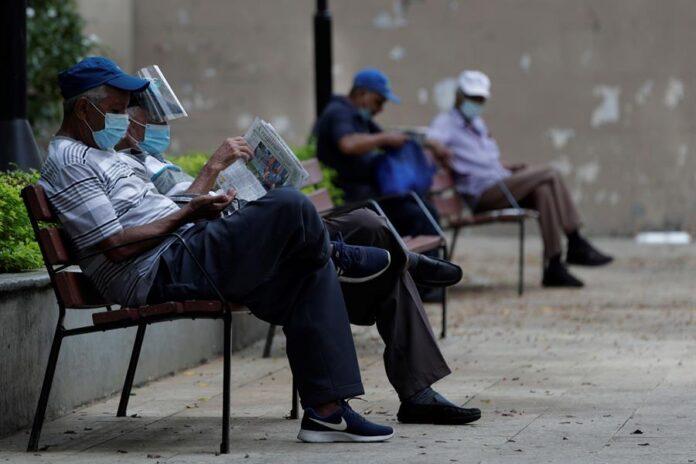 Personas leen periódicos en el parque de Santa Ana en la ciudad de Panamá (Panamá). EFE/Bienvenido Velasco/Archivo